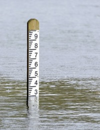 26570883 - flood level depth marker post with rain falling into the surrounding water
